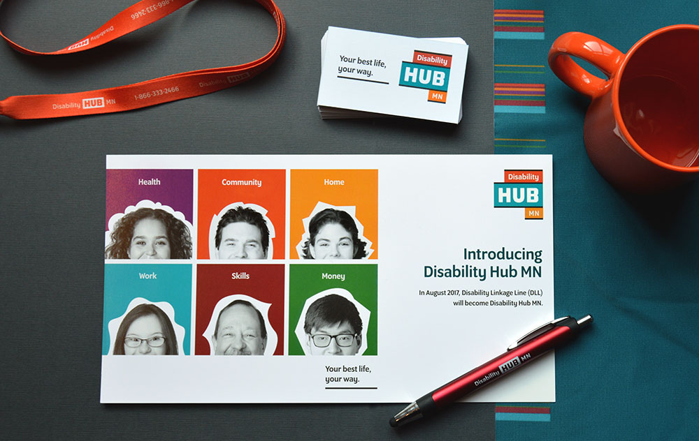 Disability Hub MN promotional materials—a lanyard, business cards, postcard and pen on a desk
