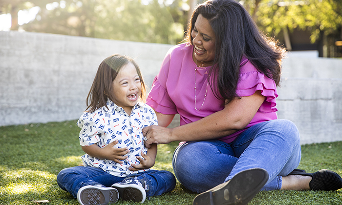 A woman and child are sitting outside in the grass. The woman is looking at the child and they are both laughing.
